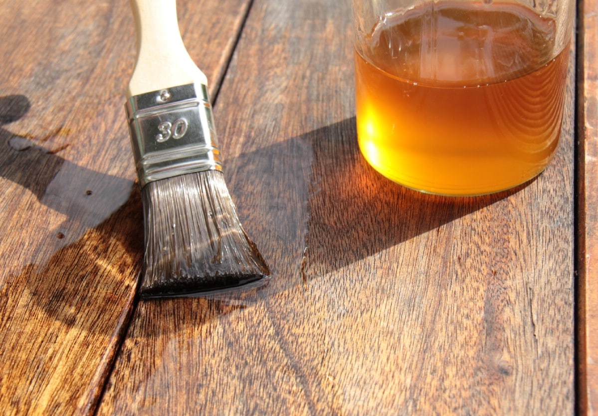 Applying linseed oil to a wooden desk.